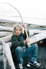 Portrait of boy at beach, leaning on driftwood, holding stick