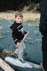 Boy at beach, standing on driftwood, holding stick