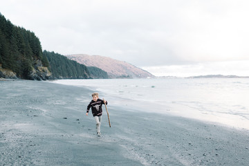 Boy running on beach, carrying driftwood