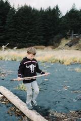 Boy at beach, balancing on log, holding driftwood