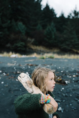 Boy on beach, holding driftwood, pensive expression