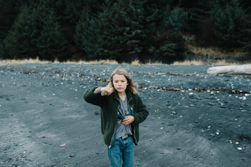 Portrait of boy on beach, holding driftwood, pensive expression