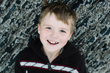 Portrait of boy, smiling, leaning against rocks