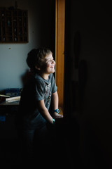 Boy at home, looking out of window, laughing