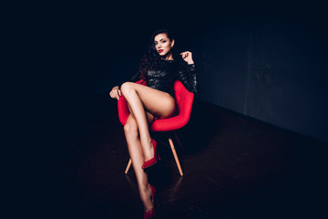 Fashion portrait. Perfect, sexy body and long legs of young woman wearing seductive lingerie posing in a sensual way in dark room by red modern chair