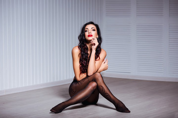Beautiful fashion portrait of young sexy brunette woman with perfect body, long legs, red lips, wearing seductive black lingerie and tights