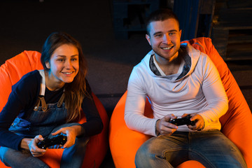 Two young gamer sitting on poufs and playing video games togethe
