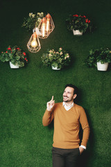 Attractive man has an idea over a green grass wall