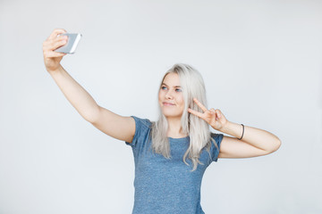 Pretty hipster girl taking selfie and smiling.