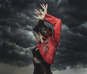 Spanish flamenco dancer with bun in hair and red coat with storm