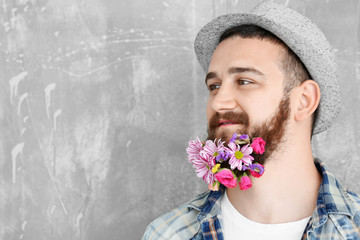 Handsome man in hat with beard of flowers on light background