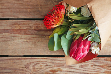 Beautiful bouquet of exotic flowers on wooden table