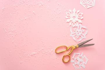 christmas theme. paper snowflkes on pink table
