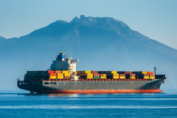 Container ship leaves the port on a background of mountains