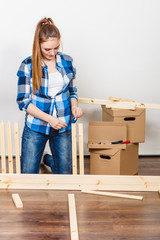 Woman moving in assembly furniture at new home.