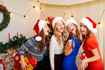 Friends sing karaoke at Christmas, New Year. Four beautiful girl