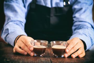 Barista holding two espresso cups
