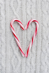 Candy canes heart on white knitted background
