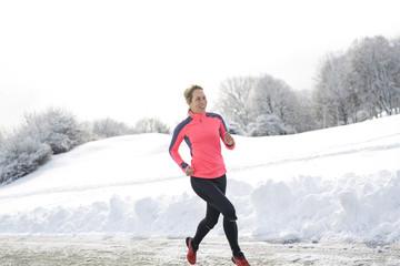 Fitness running woman in winter season