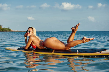 Young sexy woman lying on a surfboard