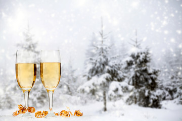 Christmas decorations and champagne against winter background