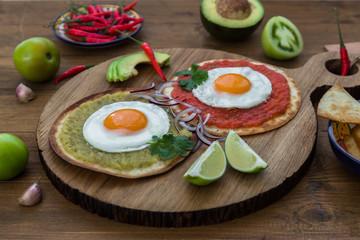 Huevos divorciados, delicious food with eggs, fresh salad and herbs  spicy  herby sauce