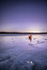 Person sitting on ice looking at stars, Finland