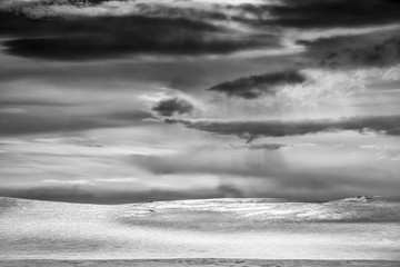 Snow covered hill and cloudscape, Finland, black and white
