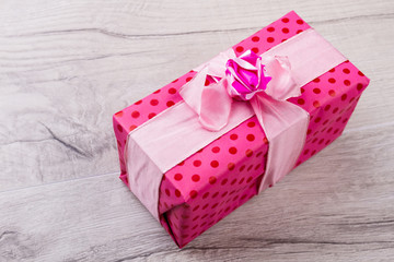 Present with ribbon and bow. Pink gift box. Bright present for bright person. Example of gift wrapping.