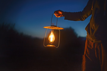 man holding the old lamp with a candle outdoors. hand holds a large lamp in the dark. ancient lantern with a candle illuminates the way on a night