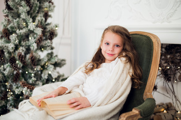 Portrait of 7 years old child reading book at home on christmas