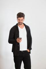 Ein junger Mann tippt auf einem Smartphone
