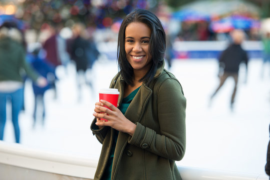 Beautiful happy smiling latin woman drinking coffee at city ice rink in front of Christmas tree. Happy young adult woman enjoying Christmas time in the city and drinking coffee and looking at camera.