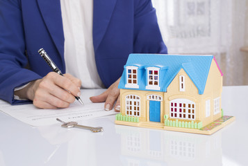 woman with house model and pen signing contract document