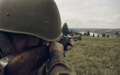 PERM, RUSSIA - JULY 30, 2016: Historical reenactment of World War II, summer, 1942. Soviet soldier aiming a rifle