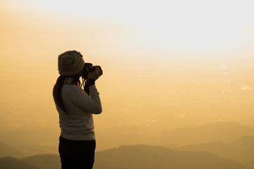 Silhouette of photographer taking picture of landscape during sunset, soft and select focus.