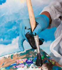 Close-up of paint brush mixing colors. Painter hand blending paints in palette before decorating wall. Art, talent, craft, hobby, creativity concept