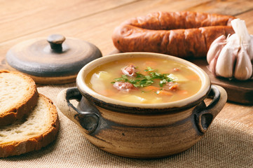 Pea soup with smoked sausage on brown wooden background.
