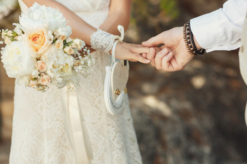 Groom holds bride's hand with paper horseshoe and heart on it