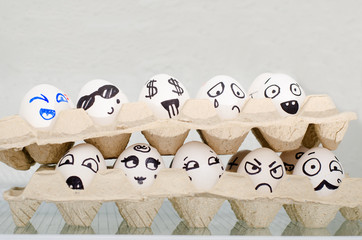 Two tray with eggs on the refrigerator shelf, painted different emotions: sadness, surprise, joy, fear