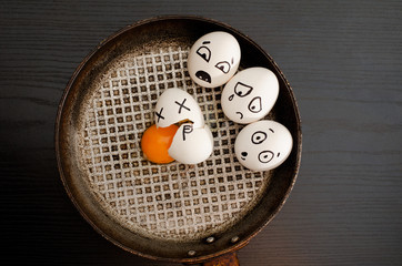 Three eggs painted with emotions, broken egg in the center of the pan, black table, space for text