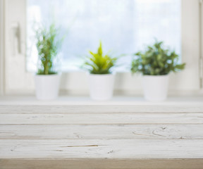 Wooden table on blurred spring window with plant pots background
