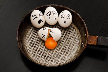 Three eggs with emotions, broken egg in the center of the pan, black table