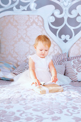 happy little girl in white dress opens gift in the Christmas decorated room
