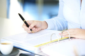 Fill the form. Close-up shot of a young businesswoman sitting at desk and sign the contract.