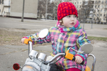 In the spring of a little girl riding a motorcycle on the street