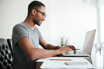 African young man using laptop and sitting at the table