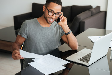 Happy man talking on cellphone while looking at documents