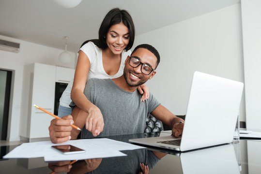Loving young couple using laptop and analyzing their finances
