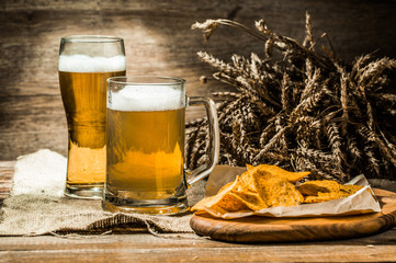 Mug, glass of beer with wheat spikelets , chips on board